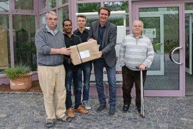 Employees of action medeor hand over a box with medical supplies to the guests from India.