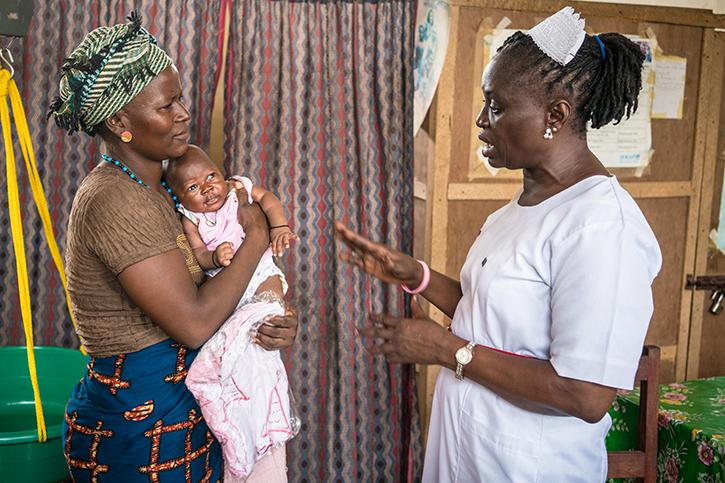 Hebamme Joyce mit einer Mutter und ihrem Kind
