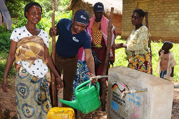 action medeor-Mitarbeiter mit Bewohnern eines Flüchtlingscamps an einer Wasserstelle