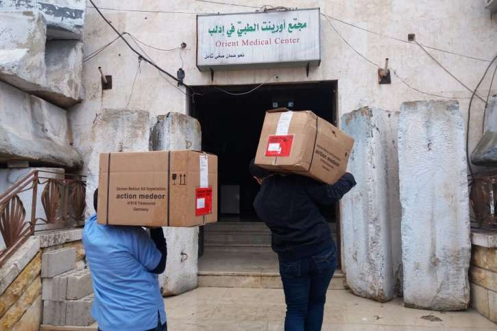Pakete einer Hilfssendung werden in ein Notkrankenhaus getragen.