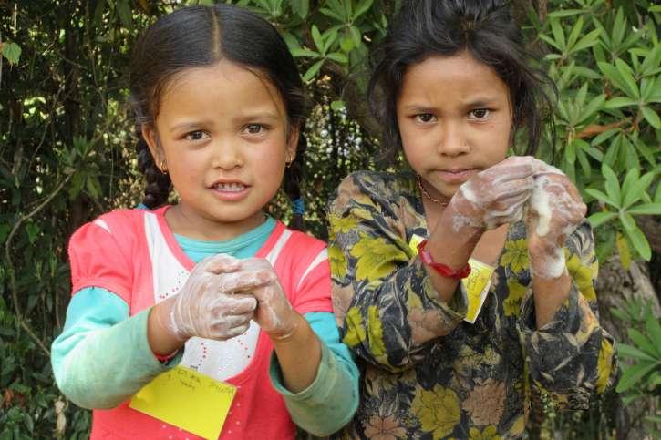 Zwei Mädchen waschen sich die Hände.