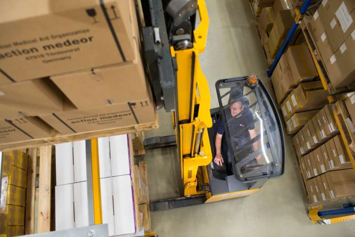 A warehouse employee handles goods of action medeor with a forklift.