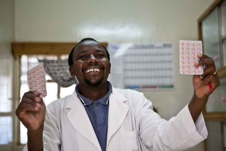 A tanzanian pharmacist holds two blister packs aloft.