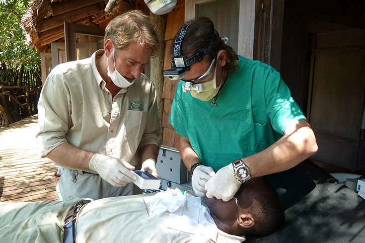 Two dentists treat a patient under a porch of a hut.