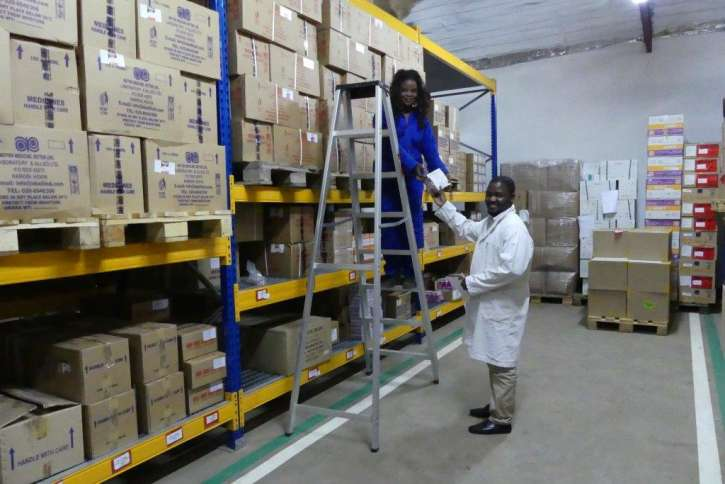 The employees of action medeor Malawi take medicines down from the shelves.