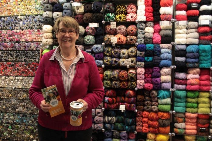 Die Besitzerin eines Wollwarengeschäftes hält die Spendendose und den Flyer der Kampagne in den Händen.