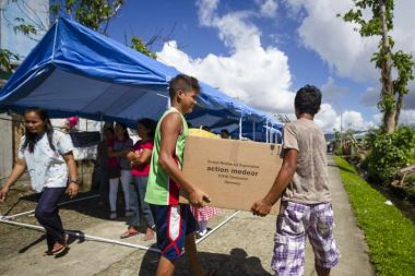 Two boys carry a package with products of action medeor on the philippines.