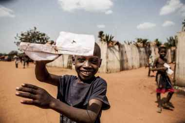 A boy in a project in Togo has folded a paper plane and shows it into the camera.
