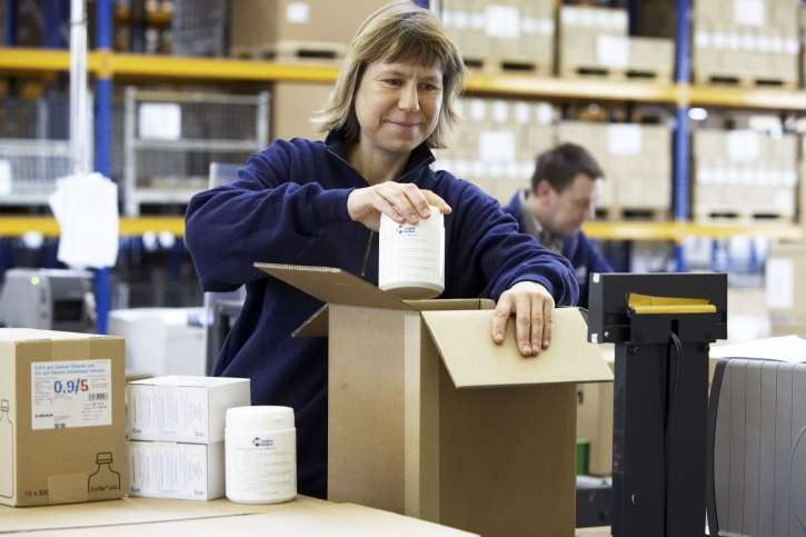 An employee in the warehouse packs products of action medeor in a box for shipping.