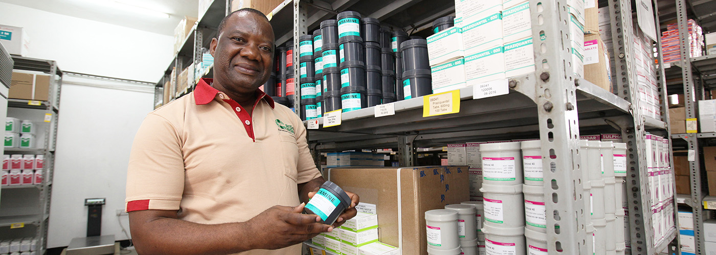 An employee of action medeor International Healthcare Tanzania presents a medicine from the warehouse in Dar es Salaam.