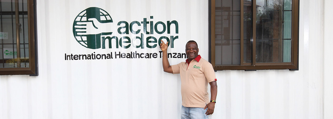 An employee of action medeor in front of a container with the logo of action medeor International Healthcare Tanzania.