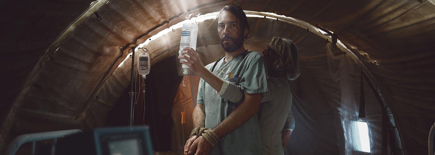 Ein Arzt steht mit gefesselten Händen in einem Behandlungszelt. Eine Frau greift ihm als Spenderin von hinten durch die Arme und legt für ihn einem dehydrierten Jungen eine Infusion an.