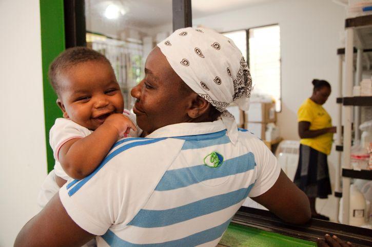 Eine Mutter trägt ihr Kind auf dem Arm.