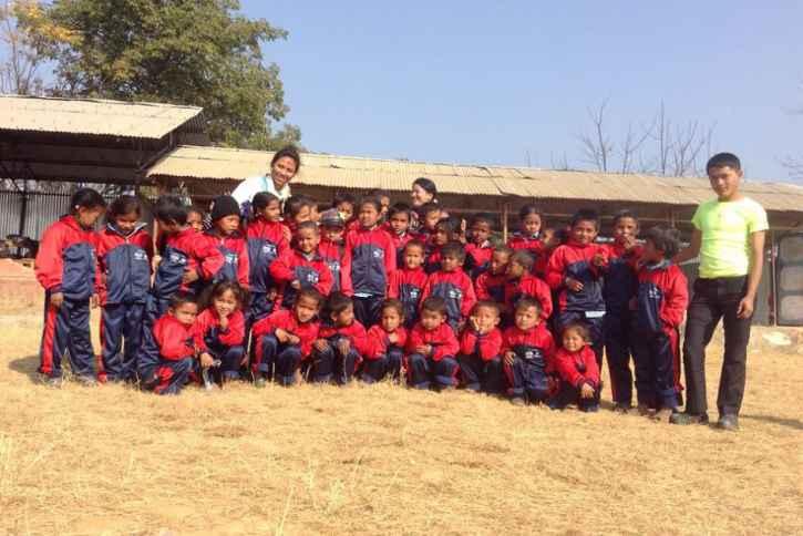 Eine Schulklasse vor ihrer Schule.