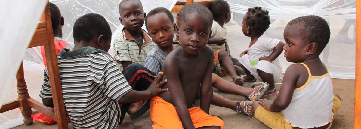 Kinder sitzen unter einem Moskitonetz während einer Aufklärungsveranstaltung über die Prävention von Malaria